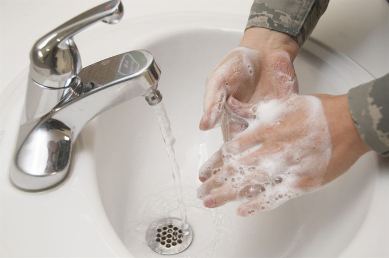 Hands being washed with soap and water in a sink.