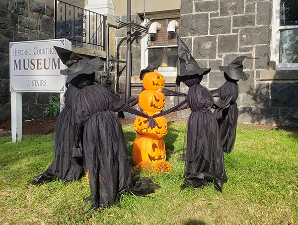 Witches surround jack-o-lanterns in front of the Columbia County Courthouse.