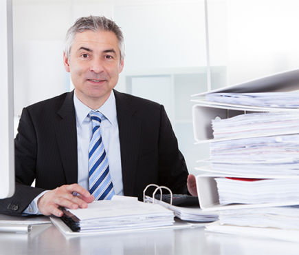 A man in a suit sits with a stack of binders on his desk.