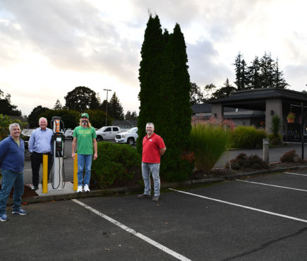 Four men stand near an Electric Vehicle Charging Station in a hotel parking lot.