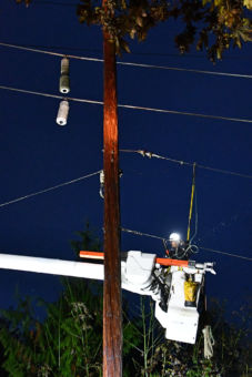 Two broken insulators hanging from a power line with a man in a bucket truck working on repairs.