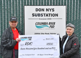 Harry Price presents a check to Terry Deaton in front of the Don Nys Substation.