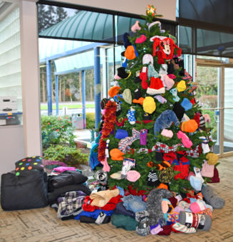 A Christmas tree decorated with warm items to be donated to charity.