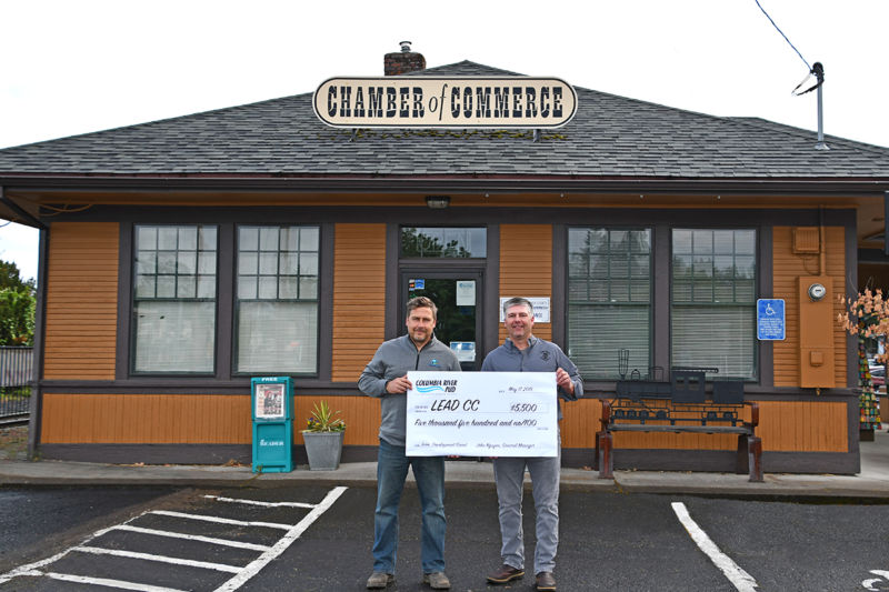 South Columbia County Chamber of Commerce Executive Director Simon Date accepts a check from Columbia River PUD Board President Jake Carter.