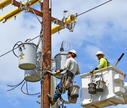 Utility workers install a transformer on a power pole.