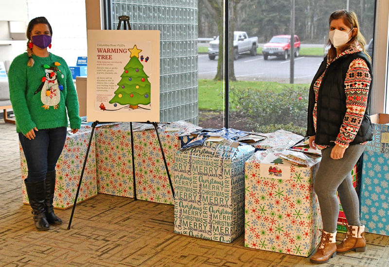 Two women stand in front of boxes of clothing for Columbia River PUD's Warming Tree.