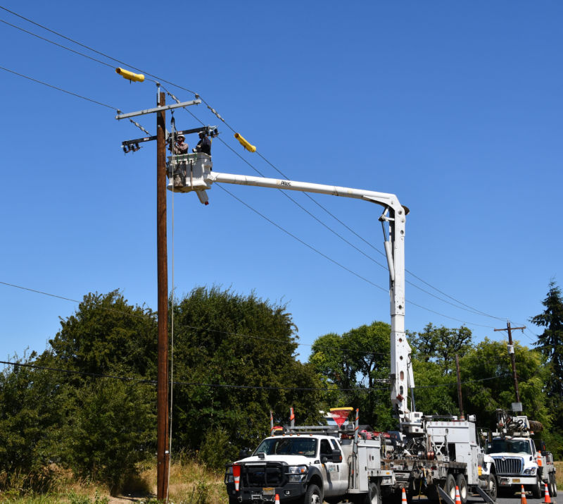 A lineman in a bucket truck works to install a re-closer on a power pole.