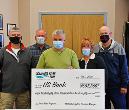 Columbia River PUD Board members and General Manager hold an oversized check.