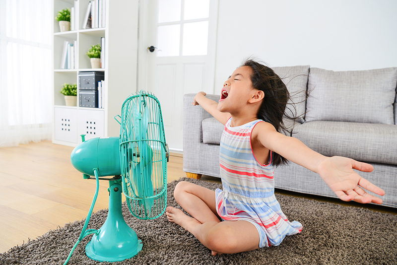A young girl cools off in front of a rotating fan.