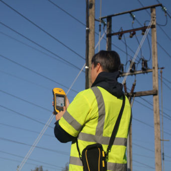 A man uses a device to test utility poles.