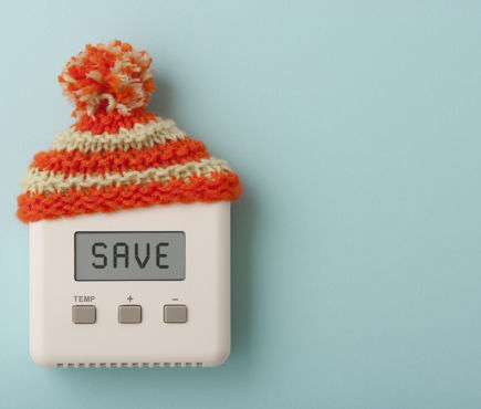 A thermostat wearing a stocking cap encouraging people to save energy.