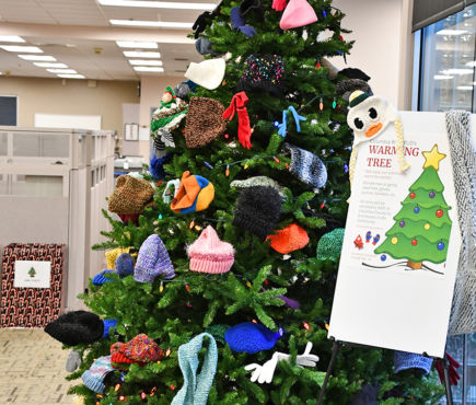 A Christmas tree with colorful hats and other items on it.