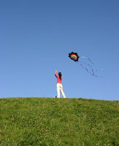 Kid flying kite on grassy hill.