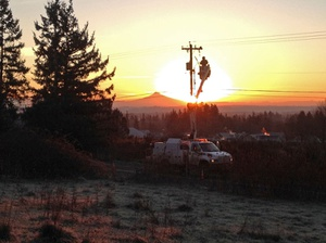 Lineman on utility pole at sunset with Mt. Hood in background