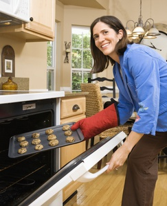 Woman placing cookies in the oven to bake