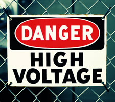 "Sign attached to wire fence to alert of ""Danger, High Voltage""."