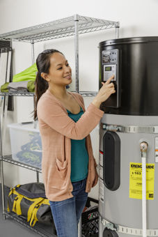 A woman adjust the temperature on her heat pump water heater inside of a garage.